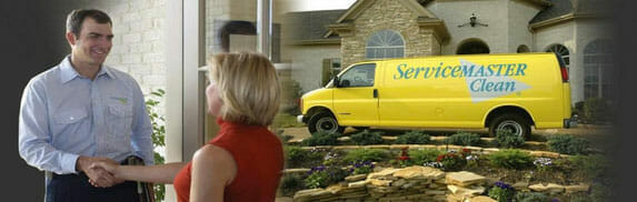 House cleaning expert shakes hands with customer. ServiceMaster company van.