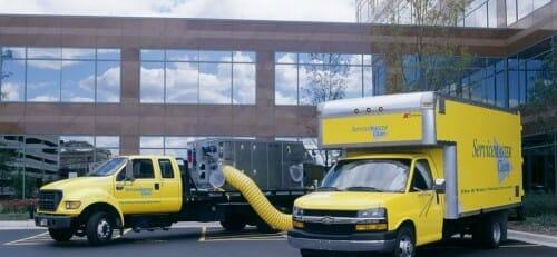 commercial disaster restoration vans in front of building