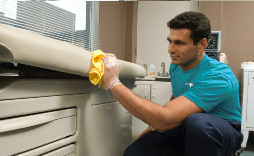 man providing hospital cleaning services in examination room