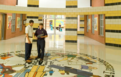 two men standing in hallway of educational facility