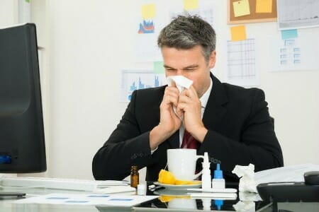 man sneezing indoor air